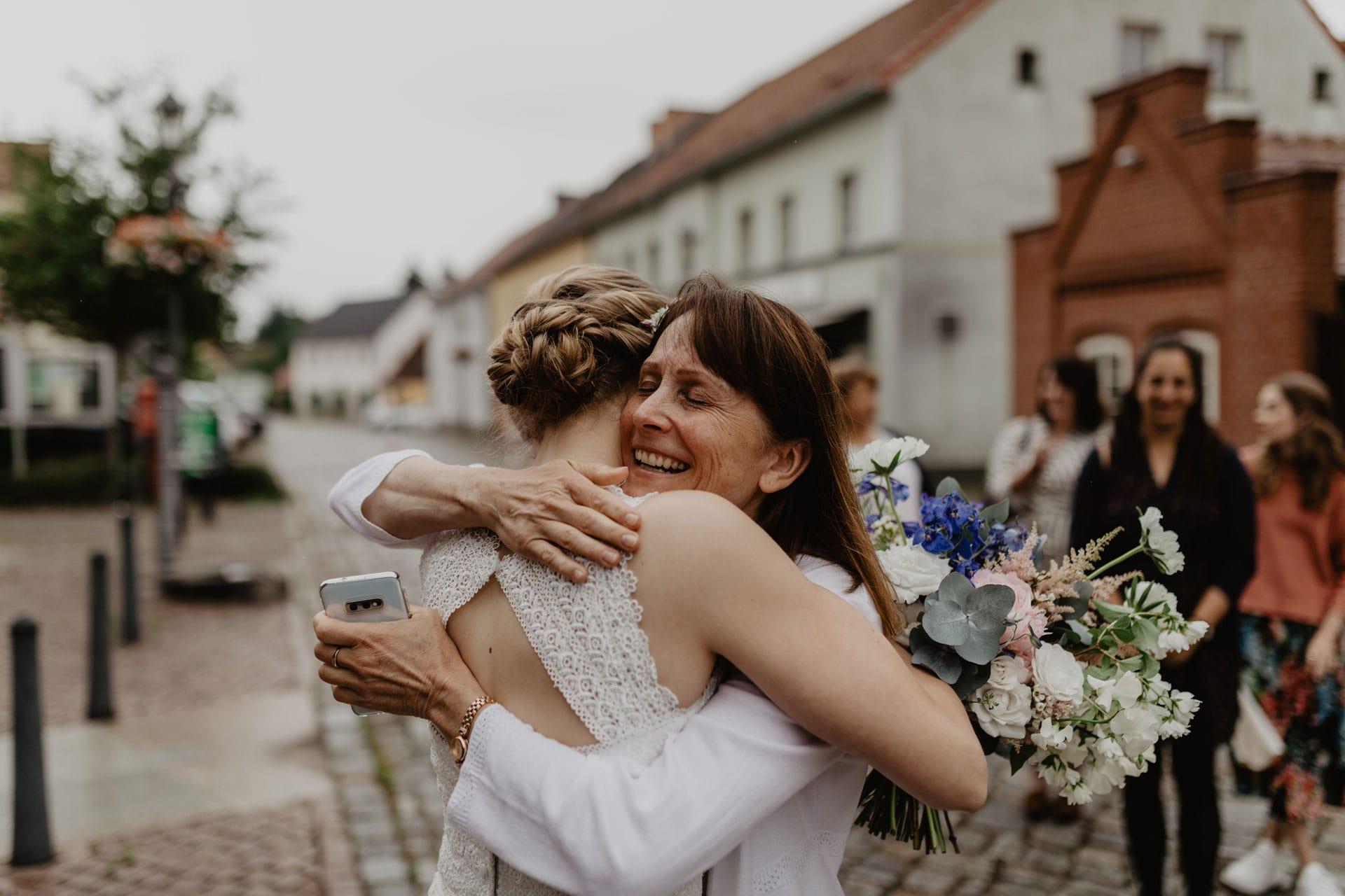 Braut und Mutter umarmen sich bei Hochzeit in Biesenthal