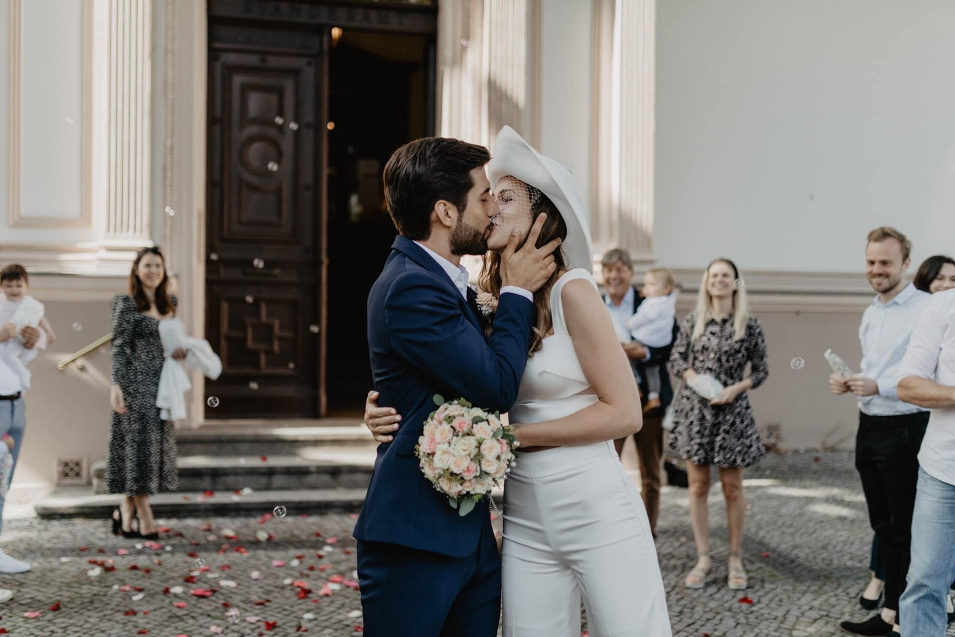 Brautpaar küsst sich nach Trauung vor Villa Kogge Standesamt Charlottenburg Berlin